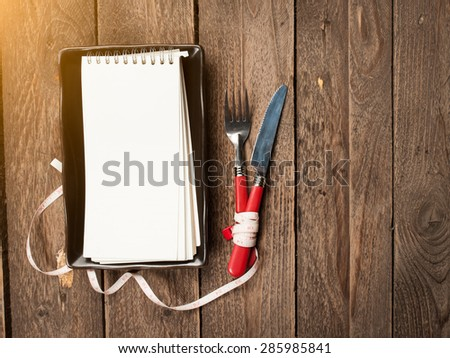 notepad for copy space and silverware on wooden table. View from above - stock photo