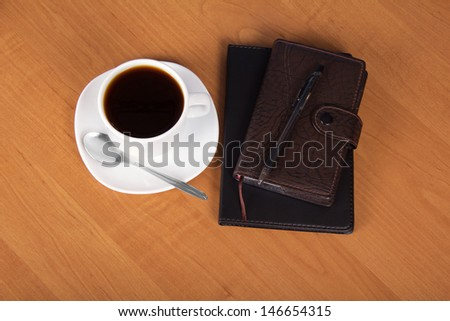 Notepad, organizer, the handle, a cup of coffee, saucer and spoon on a table