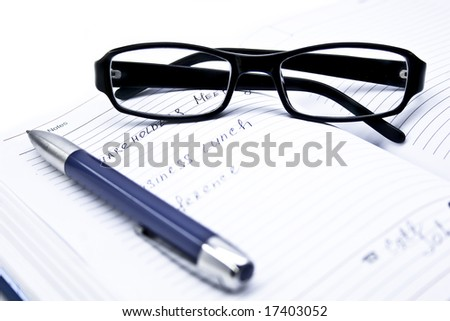 notepad, pen and glasses on a white backgraund