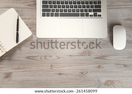 Notepad, pen, laptop and mouse on old wooden desk. View from above with copy space in vintage tone. - stock photo