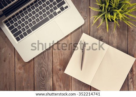 Notepad, pen, laptop and plant pot on old wooden desk. View from above with copy space in vintage tone. - stock photo