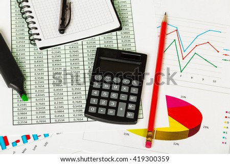 Notepad, pen, marker, pencil and calculator on the background of graphs. - stock photo