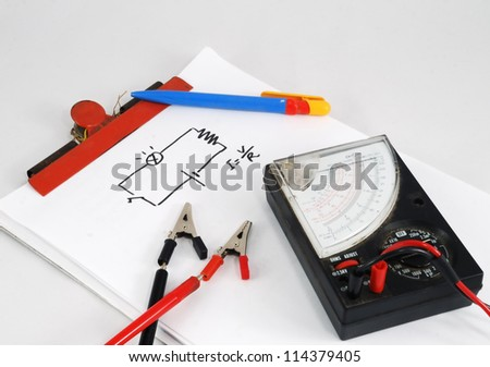 Notepad, pen, multimeter and a little schematic of Ohm's law - stock photo