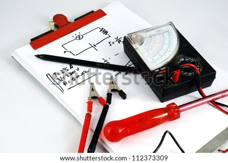 Notepad, pen, multimeter, screwdriver and a little schematic of Ohm's law - stock photo