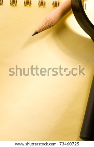 Notepad, pencil and magnifying glass isolated