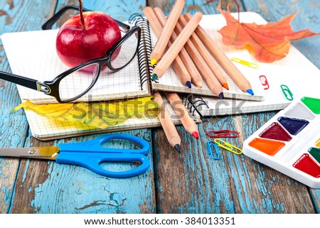 Notepad, pencils, scissors, paper clips and glasses. Office or school supplies on wooden planks painted in blue. - stock photo