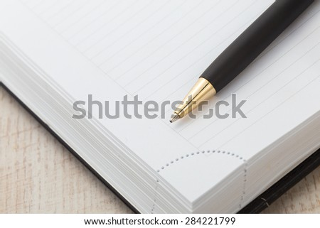 Notepad with ball pen on a wood background - stock photo