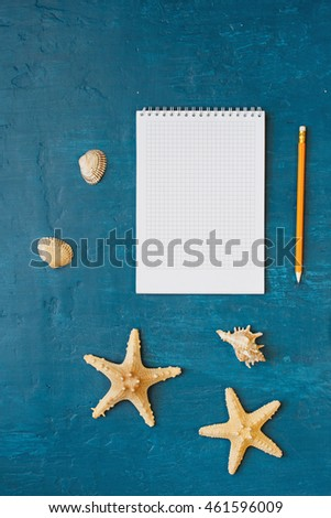 Notepad with blank page with pencil, shells and starfish on blue surface, top view. Summer background