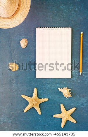 Notepad with blank page with pencil, straw hat, shells and starfish on blue surface, top view. Summer background