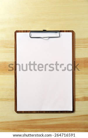 notepad with blank paper on wood table - stock photo