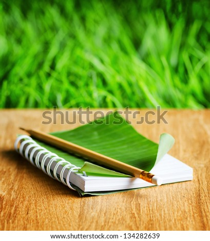 Notepad with cover of leaf lies on wooden board. - stock photo