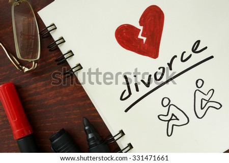 Notepad with divorce on the wooden table. - stock photo