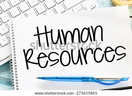 Notepad with human resource and keyboard on wooden background - stock photo