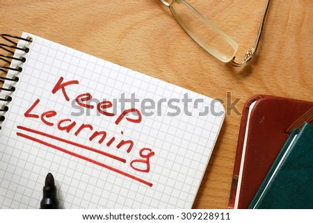 Notepad with keep learning on a wooden table. - stock photo