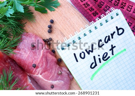 Notepad with low carb diet and fresh meat  on wooden board - stock photo