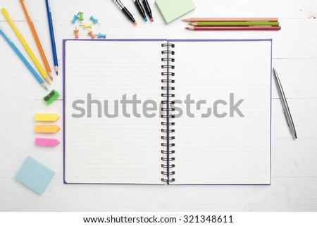 notepad with office supplies on white table view from above