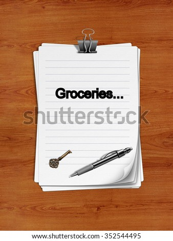 "Notepad with paper clip isolated on a wooden surface. A pen and an old key are on the paper. "" Groceries"" is written on the notepad as a reminder."