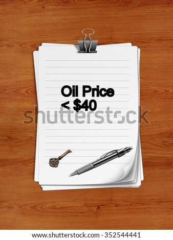 "Notepad with paper clip isolated on a wooden surface. A pen and an old key are on the paper.""Oil Price < $40"" is written on the notepad as a reminder."