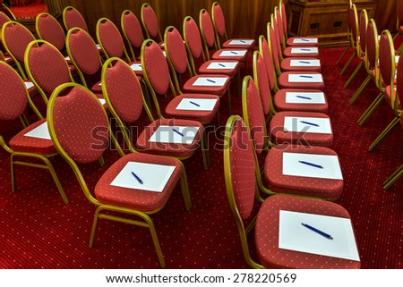 Notepad with pen for agenda on chairs in empty corporate conference room before business meeting - stock photo
