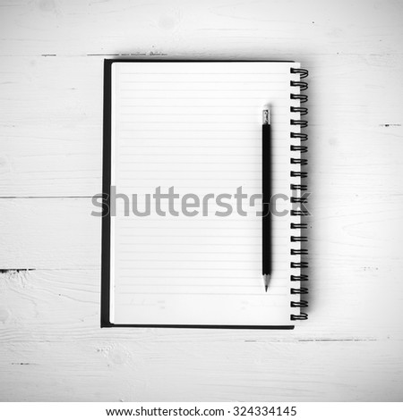 notepad with pen on white table black and white style - stock photo