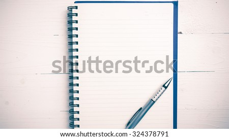 notepad with pen on white table vintage style - stock photo
