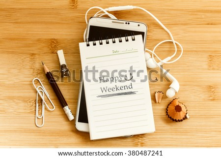 notepad with  pencil and smart phone on wooden table for happy weekend concept , overhead shot or Top view - stock photo