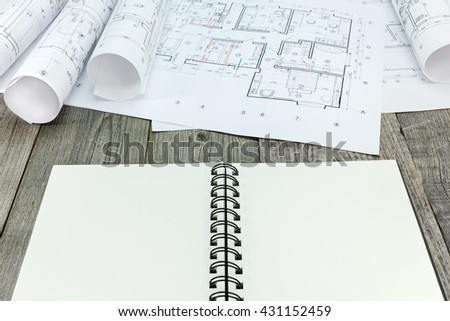 notepad with rolls of architectural blueprints and technical drawings - stock photo