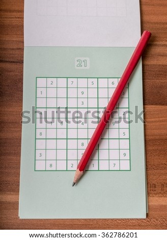 Notepad with sudoku crosswords and red pencil. - stock photo
