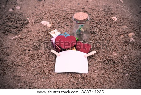 Notepaper and red heart shape on sand beach under sunset and warm light colored filter. - stock photo