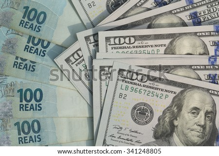 Notes of one hundred US dollars versus one hundred reais / US dollar versus the Brazilian currency - stock photo