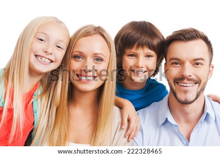 Nothing but family! Happy family of four bonding to each other and smiling while standing against white background  - stock photo