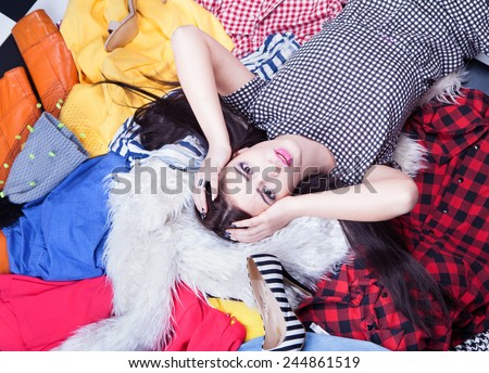 Nothing to wear concept, young attractive stressed woman lying down on a pile of clothes - stock photo