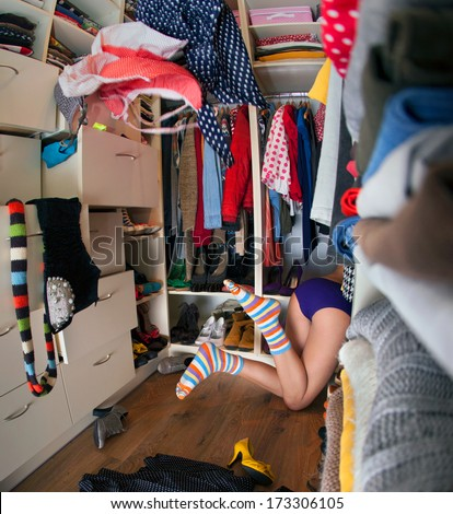 Nothing to wear concept, young woman searching for clothing in walk in closet - stock photo