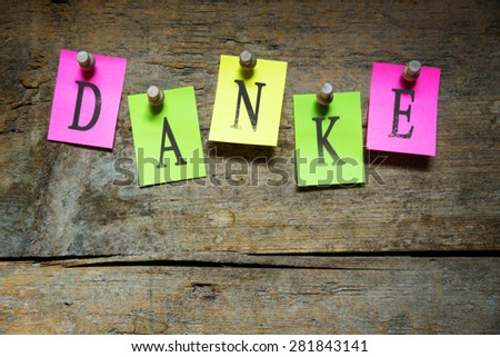 notice with the german word for thank you, wooden background - stock photo