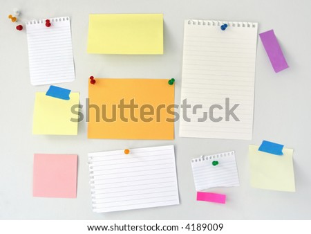 Noticeboard with blank notepaper, sticky notes, push pins. - stock photo