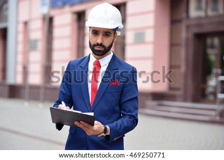 Noting every detail. Shot of a young bearded engineer making notes on his clipboard copyspace on the side
