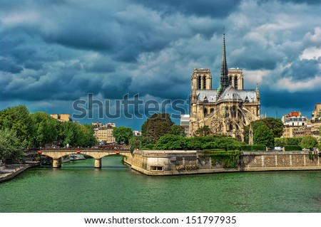 Notre Dame de Paris cathedral exterior riverside with dramatic sky - stock photo