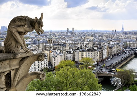 Notre Dame of Paris: Famous Chimera (demon) overlooking the Eiffel Tower at a spring day, France - stock photo