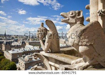Notre Dame of Paris:  Famous Chimeras overlooking the skyline of Paris at a summer day