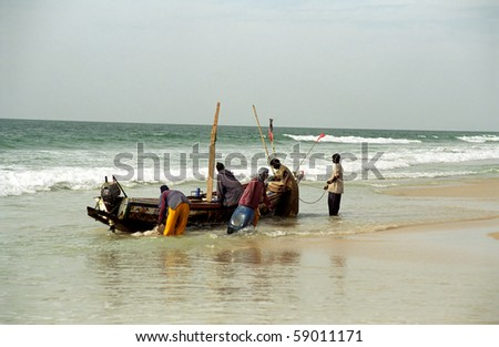 NOUAKCHOTT, MAURITANIA - JAN 5: Local fishermen arrive with their catch at January 5, 2006 in Nouakchott, Mauritania. Fresh fish is sold daily on the beach. - stock photo