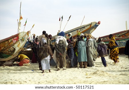 NOUAKCHOTT, MAURITANIA - JAN 5: Local fishermen sell their daily catch on the beach on January 5, 2006 in Nouakchott, Mauritania. - stock photo