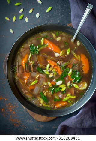 Nourishing bowl of chicken soup with vegetables - stock photo