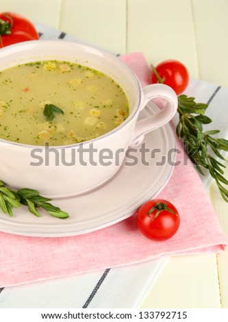 Nourishing soup in pink pan on wooden table close-up - stock photo