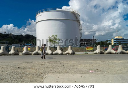 Nov2017,Point Cruz, Honiara, Solomon Islands, two men walk in front of an oil tank at the harbor, where Honiara was founded during WWII as a petrol station and depot for American army