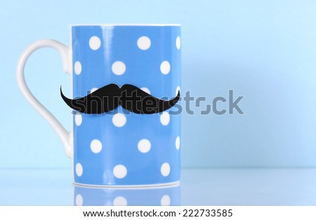 November fund raising for mens health awareness charity with mustache on blue polka dot coffee mug cup on blue background, with copy space. - stock photo