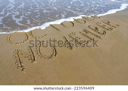 November is coming concept - inscription October and November written on a sandy beach, the wave is starting to cover the word October. - stock photo