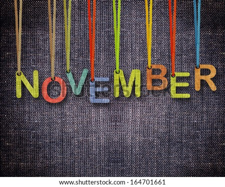 November  letters hanging strings with blue sackcloth background. - stock photo
