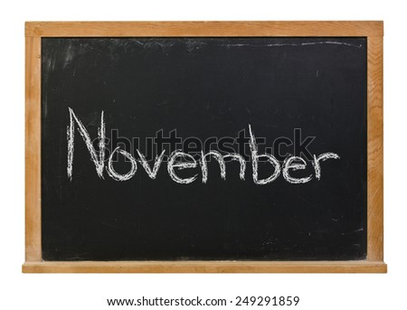 November written in white chalk on a black wood framed chalkboard isolated on white - stock photo