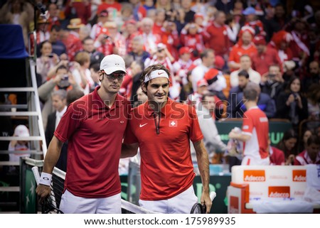 NOVI SAD - JANUARY 31: ROGER FEDERER of Switzerland and Ilija Bozoljac of Serbia during the Davis Cup match between Serbia and Switzerland, January 31 2014, Novi Sad, Serbia - stock photo