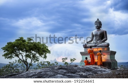 Novice Monk fire candles to the Buddha - stock photo